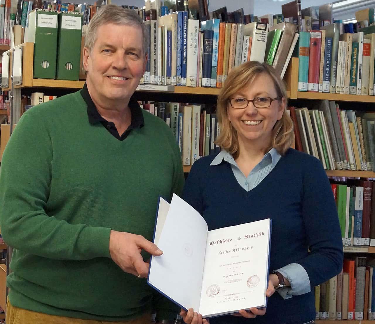 Kreisvertreter Hans-Peter Blasche übergibt einen Abdruck eines seltenen Buches über den Kreis Allenstein an die Leiterin der Bibliothek Frau Margarete Polok.